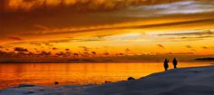 Helsinki's uniquely beautiful winter soul. A winter sunset fills the sky and the sea with shades of orange on the island of Uunisaari at the southern end of Helsinki.