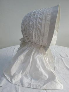 A interesting an unusual white corded summer bonnet. is shaped like a cned bonnet with a brim. ca.1860s