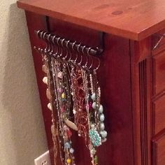 Necklace organizer made with over the cabinet door towel rack and shower curtain hooks.