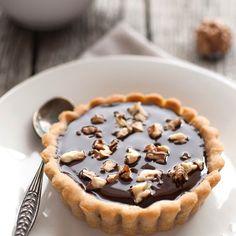 Mini-tartelettes au chocolat et aux noix – Ingrédients de la recette : 1 rouleau de pâte sablée, 150 g de chocolat noir, 15 cl de crème liquide, 20 g de beurre, 25 g de noix concassées