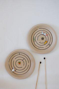 Paper plate magnet maze. Dibuja un laberinto ayudándote de un compás. Pinta y recorta una figura de papel y pégale un imán por detrás. Hazte de unos palitos de madera o de cartón y pega también imanes en ellos. Pon la figura sobre el plato con el imán hacia abajo y el palo por debajo del plato con el imán hacia arriba e intenta llevar a la figura a la meta. Un juego muy entretenido y sencillo de hacer.