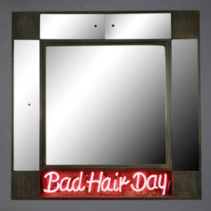 f you're having a bad hair day you might as well own up to it. This vanity cabinet isn't afraid to point out the humor in your cowlick with a bright neon sign. Constructed of wood with paneled mirrors, the vanity opens to reveal storage for all your hair-battling weapons of choice.