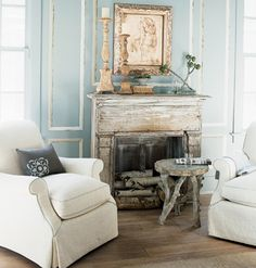 So pretty...love the shade of blue on the wal and the crisp white slipcovers juxtaposed with the primitive fireplace and stool.