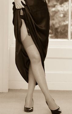 Black dress upskirt to show nude stockings and black heels. Sepia style picture.