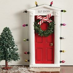 This adorable, miniature dimensional door is surrounded by lights (not actual lights) and a faux wreath with bow.  The door size measures 5high