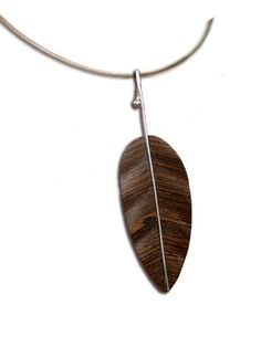 Dije Hoja Lisa 2, tallada en maderas preciosas como Bocote, Avellano, Madera de Cebra y Wenge entre otras. El Tallo es de Plata .925, hecho a mano de forma artesanal.