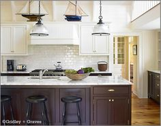Beautiful kitchen with white upper cabinets and dark wood lowers, with white subway tile backsplash.