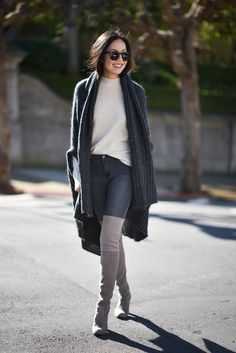Ann Taylor is wearing over the knee boots with classic skinny jeans and a long cable knit cardigan, creating a simplistic and sweet winter look. Sweater: Equipment, Wrap: Acne Studios, Jeans: J.Brand, Boots: Stuart Weitzman.