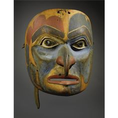 "A BELLA COOLA POLYCHROMED WOOD MASK    composed of carved wood, hide and pigments, depicting a hawk; the back secured with a wooden ""bite.""   Height 11 in."