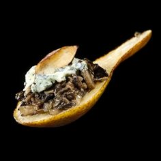 An amuse bouche made of pear with mushroom duxelles, bleu cheese and a toasted almond.