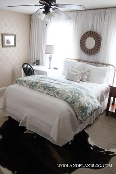 Master bedroom makeover on a budget! Wall of white curtains and a $1 Stencil wall.