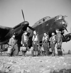 Flying Officer J F Greenam (in the centre) and his crew, photographed in front of Lancaster W4201 of No 57 Squadron at Scampton, February 1943. This image was part of a sequence taken for an Air Ministry picture story entitled 'T for Tommy Makes a Sortie', which portrayed the events surrounding a single Lancaster bomber and its crew during a typical operation.