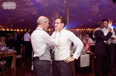 Great documentary wedding photo of the groom and his father after the speeches at their rustic tented wedding in Stowe, VT.