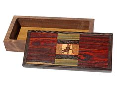 """Handmade box by J. Seaton with a lid of spalted pine, lignum vitae, black palm, cocobolo, walnut, and wenge. The body is made from walnut and is 1 1/2""""D. Each box is completely handmade using rare and exotic woods. Each is created spontaneously and no two are ever exactly alike. Each is sanded seven times to a satin smooth surface and finished in an oil and wax finish. Size: 10 3/4""""L x 4 7/8""""D x 2 5/8""""H  Price: $375.00  -- on ScrimshawGallery.com #woodworking #jewelrybox"""