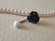 Rose Black Belly Ring 14ga Navel Ring Stainless Steel Body Jewelry. This cute little flowers are on a 14ga surgical stainless steel belly ring. With acrylic white ball top. The flower is approx 10mm. These tiny flowers fit just right inside the navel! Show off your piercing this summer with this cute little flower. Specifications: * 14ga Surgical Steel * 10mm Rose * Acrylic Ball Top.