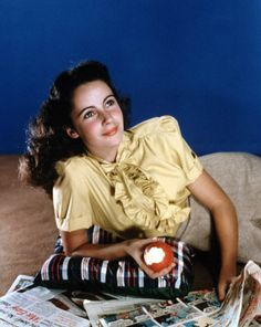 A young Elizabeth Taylor reads the Sunday comic strips - c. 1940s