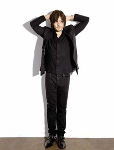 Norman Reedus,  like a police stance ok now I am going to frisk you and this wont hurt much at all.....