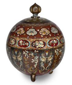 A large cloisonné enamel oviform vessel and cover Meiji period (late 19th century) Set on tripod feet, worked in gilt and silver wire, the body with two wide bands of lobed panels enclosing assorted floral motifs and stylised insects and birds, above a band of lappet panels containing alternating confronted dragons and phoenix birds on a transparent enamel ground flecked with aventurine, the cover similarly decorated and surmounted with a domed-shaped finial