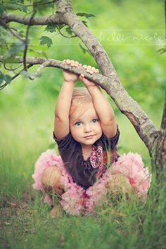 having arms up on the branch rather than in her lap adds interest to the picture...look for ways child can interact with the surroundings