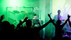 Photo of a band performing, the crowd cheering with hands in the air. free download at skitterphoto.com