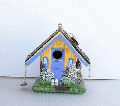 Este es un poco cutie! Es una pajarera pequeña amarillo y lavanda. La casa viene con su propia colmena colgando de los aleros, un columpio, un letrero que dice Birdie B-n-B y algunas botellas de leche en la escalinata frontal. Este comedero para pájaros está construido en pino pintado con pinturas acrílicas y tiene varias capas de capa clara rociado sobre él para que usted puede ponerlo fuera de las aves silvestres. Esta es una casa pequeña pero es lo suficientemente grande como para dar…
