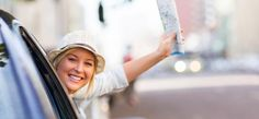 Happy female tourist waving goodbye from car window with map