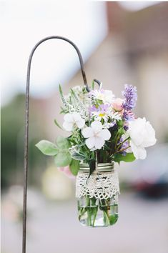 Jam jar flowers arrangements by day - hanging tea light lanterns by night.  Switch it up!