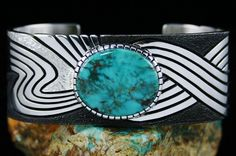 Alton Bedonie Fox Turquoise Bracelet #AltonBedonie #Cuff  To best describe this fine bracelet is Alton's ability to create art nouveau in hand made jewelry. A fine rare Fox turquoise mined in the 1970's is set in a high hand chiseled bezel. The natural gem is a classic representation of the mine, gorgeous deep blue green with wispy reddish-brown and chocolate matrix. It sits on a marvelous shank. The shank is deeply hand textured and oxidized.