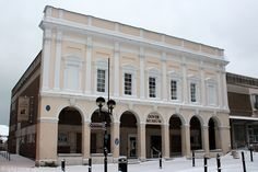 The Dover Museum Listed Building in Winter, Market Square, Kent, England, UK. Museum facade is the only remaining part of 1846 Victorian Market Hall that was built on site of 1746 Town Gaol. Damaged by shells and bombs in World War II. New building contains Silver Screen Cinema, entrance in Gaol Lane on left. Discovery Centre and Dover Library to the right, Ellie Cafe Bar (pub) to the left. Snow in February, 2012. Urban Dover Architecture and History. See: http://www.panoramio.com/photo/85255101