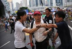 Pro-democracy protesters argue with a man as he walks away from an area blocked by protesters outside the government headquarters office in Hong Kong, China, October 9, 2014. REUTERS-Carlos Barria