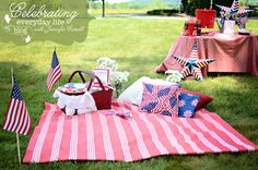 4th of July picnic with red & white striped blanket, partiotic pillows, red picnic basket, us flag, 4th of July cookies