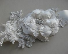This belt is handmade by me on the ivory satin ribbon. Ivory sash done with IVORY flower rose made of satin, lace, crystal rhinestones.    Ribbon: 2 inch wide, approximately 2 yards.  Flower size is 4.3      Each flowers is handmade so every is different and unique!    *** Any creation can be costumized.    *** I accept custom orders as well. Please contact me if you have any idea or suggestion.    *** For any questions please contact ill be very happy to help you!    It will arrive in a box…