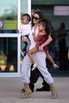 Impressive style skills: Kim managed to carry her children despite wearing stiletto army-inspired boots