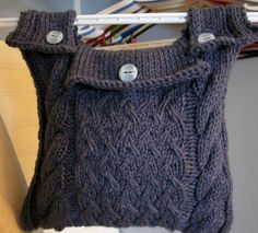 "Free Knitting Pattern for Hanging Storage Bag - Originally designed to hold clothespins while hanging on a line or hanger, this cabled bag could easily be adapted for other uses where you want a hanging tote bag. I thought it might be useful to hang on a walker for example. About 12"" x 12"" (30cm x 30cm). Designed by Catherine Marcoux"