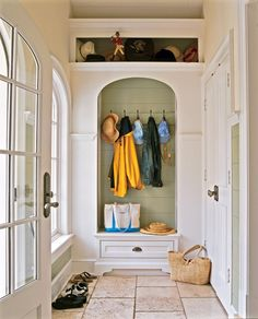 Coats and hats hang from hooks in an arched niche in the mudroom. The drawer below stores more gear. - Traditional Home ®/ Photo: Tria Giovan / Design: Serena Crowley