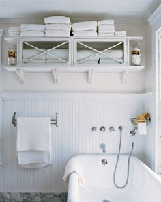 Towel Cabinet - A wooden flea-market cupboard makes a great towel cabinet. Use the top of the cabinet for extra storage. Keep your regular supply in the glass-fronted cabinet. Having all towels visible makes it easy to keep track of your inventory. Open shelves on the sides hold glass jars full of cotton balls and soaps.