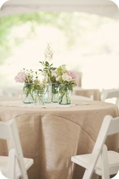 We will have either sand, gray or white colored linens with a variety of jars and bloom vases of white, yellow, and pink flowers in each one. There will also be the white washed wood planks, drift wood, and candles.