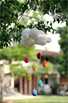 A mobile with white cloud and rainbow raindrops