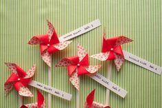 by Jordan Ferney    Make a cute and easy display for your pinwheel escort cards. For this project, we used a pretty floral origami paper. Origami works great because there is a different pattern on the front than there is on the back.        Supplies for Pinwheels:  1. Floral Origami Paper $5  2. Dowels or Pencils (the pencils work well because you can use the eraser for the pin.) $4  3. Map Pins $4  4. Scissors  5. Strips of ca...