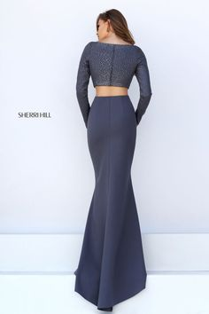 Combine elegance with sex appeal in the Sherri Hill 50209 two-piece prom dress. This jersey jersey ensemble showcases an all over beaded crop top with a high square neckline. Long fitted sleeves lead to the full back. The full-length skirt flows into a smooth sweep train and features a provocative mid-thigh side slit.