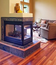 A transitional peninsula fireplace design from Interior Dimensions features a tile hearth, tile along the perimeter of the fireplace, a shelf, and is located on Brazilian Teak hardwood flooring.