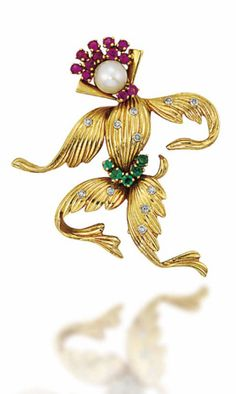 A GEM-SET NOVELTY CLIP BROOCH, BY VAN CLEEF & ARPELS Modelled as an exotic dancer, the fluted body with brilliant-cut diamond and circular-cut emerald accents, to the cultured pearl head with circular-cut ruby collar and headdress, circa 1950, 4.3cm long  Signed VCA for Van Cleef & Arpels, no.1V427.4