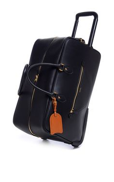 This duffle bag by **Mark Cross** is rendered in bridle leather and features a two-wheel system with a telescoping handle in zip compartment, two top handles, an additional side handle, two exterior zip pockets and a cognac luggage tag.