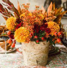 fleurs automnales et gratte-cul dans un vase en tronc