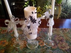 Pillar and matching tapers in sheer ribbon with silver edging. Black Crystal flowers adorn them.