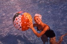 1960s SMILING WOMAN IN SWIMMING POOL WEARING RUBBER BATHING CAP HOLDING PLASTIC BEACH BALL