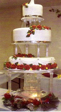 The 3-tier of this cake are placed on columns / pillars above a flowing fountain and decorated with beautiful red roses, dark green leaves, ...