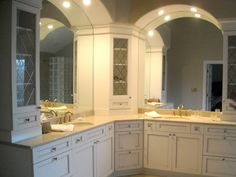 An upper cabinet. Sometimes the spot where two counters meet can be awkward. This angled cabinet marries the two arched mirrors and the vanities.