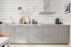 Una cocina gris con toques dorados