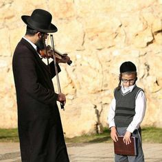 A Jewish father playing the violin to his son.jew